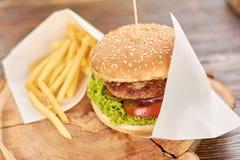 汉堡用在木头的油煎的土豆 免版税库存照片