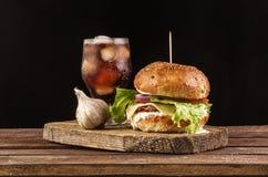 汉堡用大蒜和可乐在木切板有copyspace的 库存图片