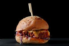 汉堡用牛肉和乳酪在木头和被隔绝的黑背景 库存照片