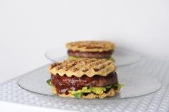 汉堡用牛肉砍,鳄梨调味酱捣碎的鳄梨酱,樱桃调味汁,在格栅的土豆小圆面包 奶油被装载的饼干 图库摄影