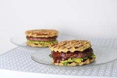 汉堡用牛肉砍,鳄梨调味酱捣碎的鳄梨酱,樱桃调味汁,在格栅的土豆小圆面包 奶油被装载的饼干 免版税图库摄影