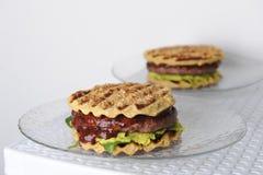 汉堡用牛肉砍,鳄梨调味酱捣碎的鳄梨酱,樱桃调味汁,在格栅的土豆小圆面包 奶油被装载的饼干 库存照片