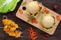 汉堡用肝脏炸肉排、蕃茄、腌汁、莴苣、辣调味汁和一个软的小圆面包与芝麻籽在切板和土豆 免版税图库摄影