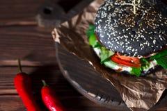 汉堡用黑小圆面包,在牛皮纸和红辣椒在黑褐色木背景 库存照片