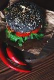 汉堡用黑小圆面包,在牛皮纸和红辣椒在黑褐色木背景 库存图片
