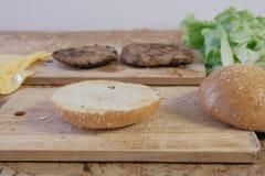 汉堡的准备的产品:小圆面包,炸肉排,乳酪,沙拉,在桌上 侧视图 免版税库存图片