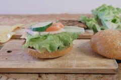 汉堡的准备的产品:小圆面包,炸肉排,乳酪,沙拉,在桌上 侧视图 免版税库存照片