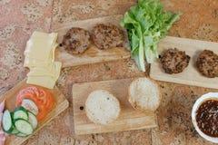 汉堡的准备的产品:小圆面包,蕃茄,黄瓜,炸肉排,乳酪,沙拉,调味汁,在桌上的烟肉 顶层 库存图片