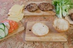 汉堡的准备的产品:小圆面包,蕃茄,黄瓜,炸肉排,乳酪,沙拉,调味汁,在桌上的烟肉 顶层 免版税库存图片