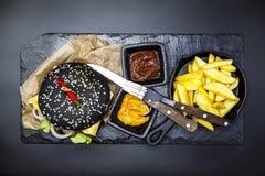 黑汉堡的套 石板材与:黑汉堡卷切片水多的大理石牛肉,被熔化的乳酪,与法国fr的新鲜的沙拉 库存图片