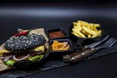 黑汉堡的套 石板材与:黑汉堡卷切片水多的大理石牛肉,被熔化的乳酪,与法国fr的新鲜的沙拉 图库摄影