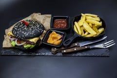 黑汉堡的套 石板材与:黑汉堡卷切片水多的大理石牛肉,被熔化的乳酪,与法国fr的新鲜的沙拉 免版税库存照片