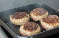 汉堡,在一个煎锅的牛肉在烹调表面在厨房里 库存照片