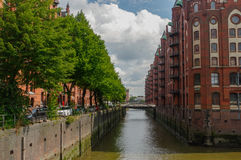 汉堡,德国- 2015年7月18日:历史的Speicherstadt房子和桥梁运河与amaising的skyview的晚上在战争 免版税库存照片