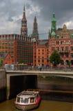 汉堡,德国- 2015年7月18日:运送在历史的Speicherstadt房子和桥梁运河与amaising的skyview的晚上 免版税库存图片