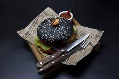 黑汉堡 与黑卷切片的一个汉堡水多的大理石牛肉、被熔化的乳酪、新鲜的烤肉的沙拉和调味汁 一个汉堡 图库摄影