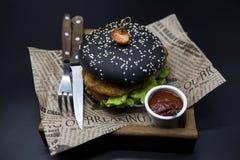 黑汉堡 与黑卷切片的一个汉堡水多的大理石牛肉、被熔化的乳酪、新鲜的烤肉的沙拉和调味汁 一个汉堡 免版税图库摄影