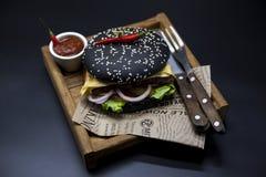 黑汉堡 与黑卷切片的一个汉堡水多的大理石牛肉、被熔化的乳酪、新鲜的烤肉的沙拉和调味汁 一个汉堡 免版税库存图片