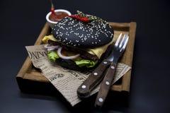 黑汉堡 与黑卷切片的一个汉堡水多的大理石牛肉、被熔化的乳酪、新鲜的烤肉的沙拉和调味汁 一个汉堡 库存图片