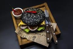 黑汉堡 与黑卷切片的一个汉堡水多的大理石牛肉、被熔化的乳酪、新鲜的烤肉的沙拉和调味汁 一个汉堡 免版税库存照片