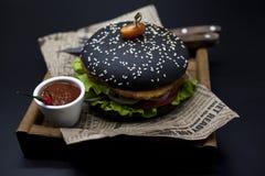 黑汉堡 与黑卷切片的一个汉堡水多的大理石牛肉、被熔化的乳酪、新鲜的烤肉的沙拉和调味汁 一个汉堡 库存照片