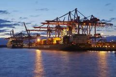 汉堡-在终端的集装箱船在晚上 免版税库存照片