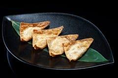 汉语在一个黑色的盘子的油煎的饺子 免版税库存图片