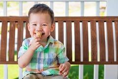 汉语年轻的混合的族种和享用他的冰淇淋锥体的白种人男孩 免版税图库摄影