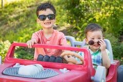 汉语年轻的混合的族种和戴太阳镜的白种人兄弟使用在玩具汽车 免版税图库摄影