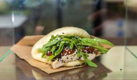 汉语蒸与豆腐、芝麻菜和蕃茄的小圆面包三明治在 免版税库存图片
