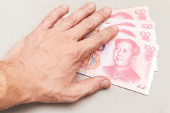 汉语100元人民币钞票和男性手 库存图片