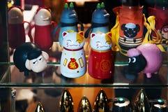 汉语 日本纪念品 小雕象白色和金黄猫带来好运 金黄Maneki Neko猫或欢迎吉祥人 图库摄影