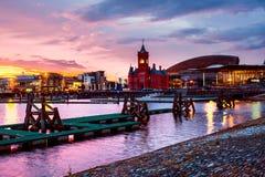 江边在晚上在加的夫,英国 与威尔士千年中心的日落五颜六色的天空 图库摄影