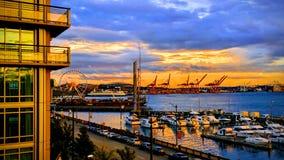 江边日落在有弗累斯大转轮、起重机,&小船的西雅图 免版税图库摄影