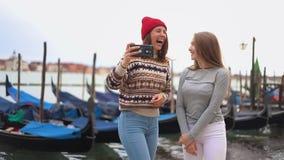 江边的两年轻女人有小船的在电话和看看被拍摄照片 股票视频