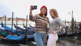 江边的谈话两的年轻女人有小船的和采取selfie 股票视频