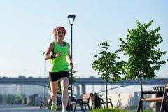 江边的连续妇女 早晨跑步 运动员火车 免版税库存照片