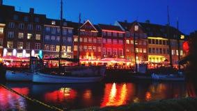 江边Nyhavn的浪漫美好的晚上视图在哥本哈根 反射明亮的灯塔和餐馆 免版税图库摄影