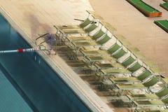 水池和sunbeds在晚上 免版税库存图片
