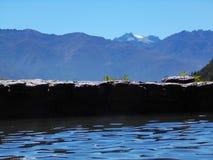 池塘被堆积的岩石墙壁在多雪的山峰前面的 库存图片
