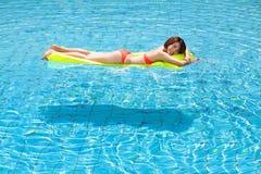 池松弛游泳妇女 免版税库存图片
