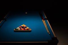 水池球和暗示在一张蓝色台面呢桌上 免版税库存照片