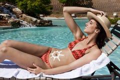 水池的太阳晒黑的妇女 免版税库存图片