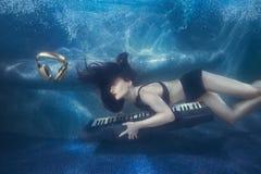 水池的女孩与钢琴 免版税图库摄影