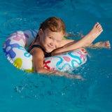 水池的小女孩与橡胶环 免版税库存照片