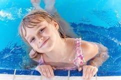 池的微笑的小白肤金发的女孩 库存照片