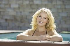 水池的愉快的白肤金发的女孩 库存照片