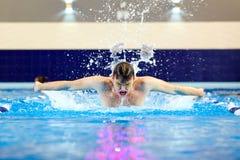 水池的游泳者游泳蝴蝶里面 运动员火车wate 免版税图库摄影