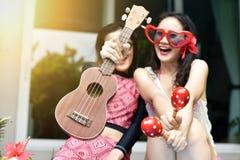 池边聚会,愉快的妇女喜欢演奏比基尼泳装微笑的乐器由游泳池,女朋友和笑 免版税库存图片