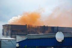 污染与橙色烟的大气和烟雾,从冶金植物的很多烟的老工厂 免版税图库摄影